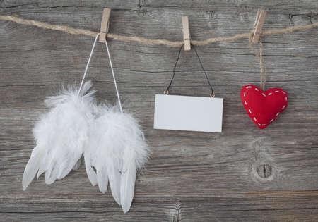 angel de la guarda: Alas del ángel con el corazón y nota en blanco sobre fondo de madera gris Foto de archivo
