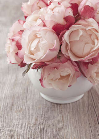 antique vase: Pink roses on wooden desk