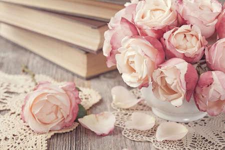 Las rosas rosadas y libros antiguos sobre el escritorio de madera