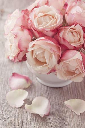 Rosa Rosen und Blütenblätter auf Holz-Schreibtisch
