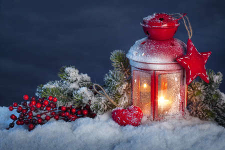 Burning lantern in the snow at night Stock Photo