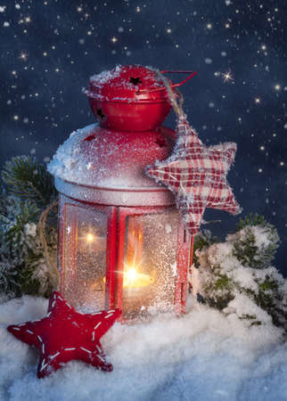 Burning lantern in the snow at night photo