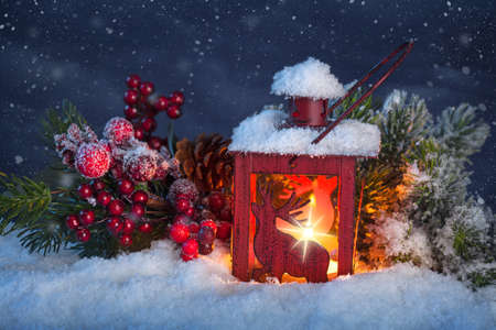 winter evening: Burning lantern in the snow at night Stock Photo