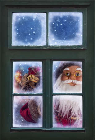 Santa Claus looking through a frosted window photo