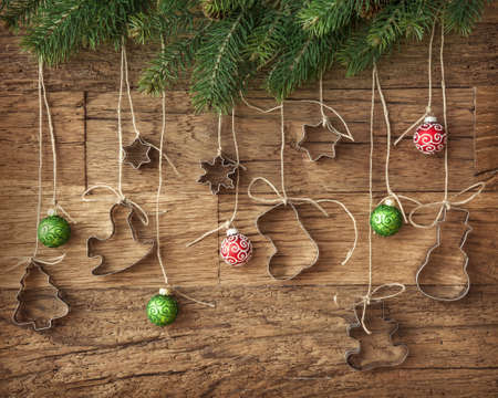 Cookie cutter and christmas baubles on wooden background photo