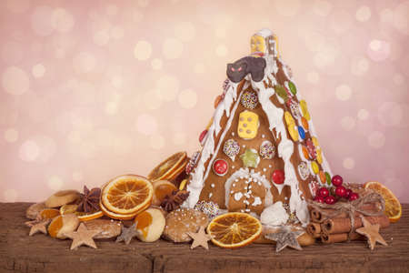 heap snow: Gingerbread house on pink sparkle background Stock Photo