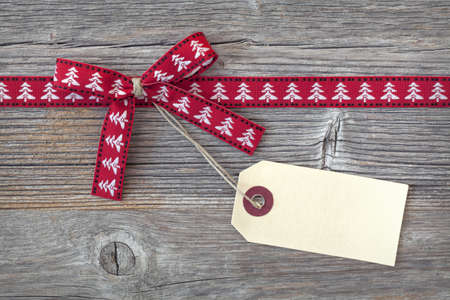 Red ribbon with a tag on wooden background