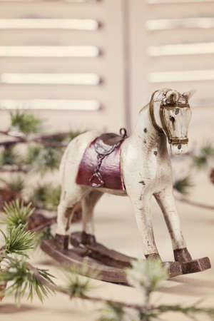 Wooden rocking horse on white table photo