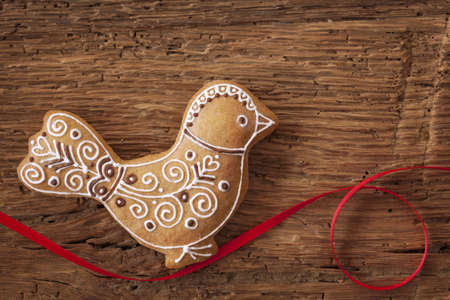 Gingerbread bird cookie on wooden background photo