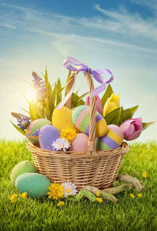Basket with easter eggs  on green grass photo