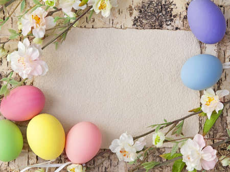 easter message: Easter eggs and blank note on wooden background