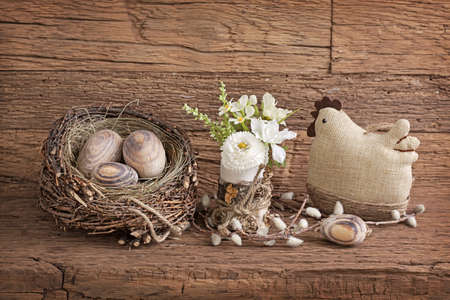 brown pussy: Easter eggs in nest and flowers  on wooden background
