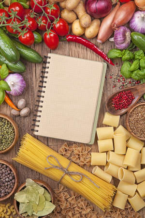 Assortment of fresh vegetables and blank recipe book on a wooden background photo