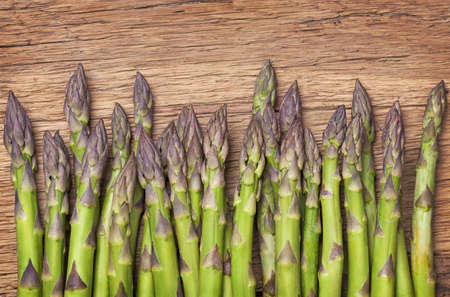 Green asparagus on a wooden background photo