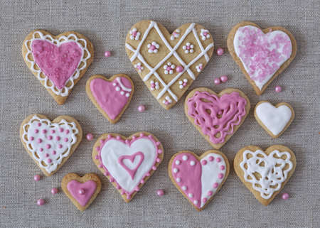 homemade cookies: White and pink heart cookies on a grey fabric background