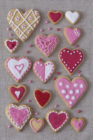 Red and pink heart cookies on a grey fabric background photo