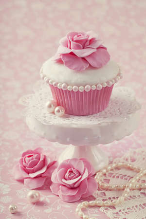 pink cake: Cupcake with rose flower on a stand Stock Photo