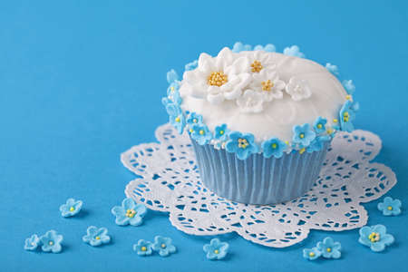 Cupcake with white and blue flowers on blue background photo