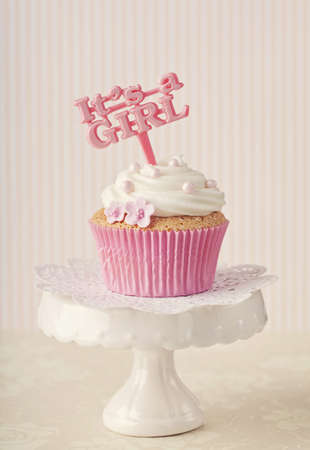 its a girl: Cupcake with a cake pick on a stand Stock Photo