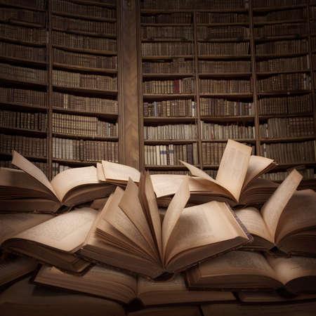 図書館: テーブルの上の開いた本の杭