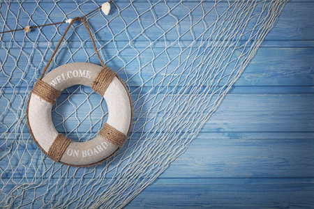 fishing nets: Life buoy decoration on blue shabby background Stock Photo