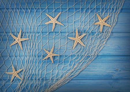 redes pesca: Seastars en la red de pesca sobre un fondo azul Foto de archivo