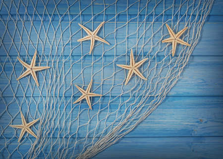 with ocean: Seastars on the fishing net on a blue background