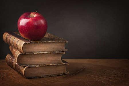 木製のテーブルの上の赤いリンゴ、書籍のスタック 写真素材