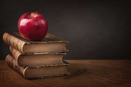 pile of books: Stack of books and red apple on wooden table