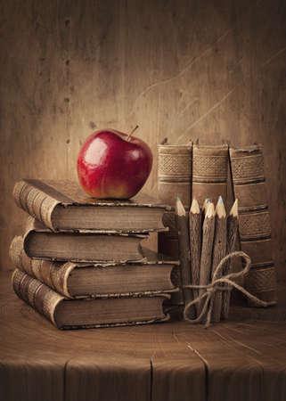 moudrost: Stack knih a červené jablko na dřevěném stole