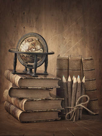 old pencil: Stack of books and globe on wooden table