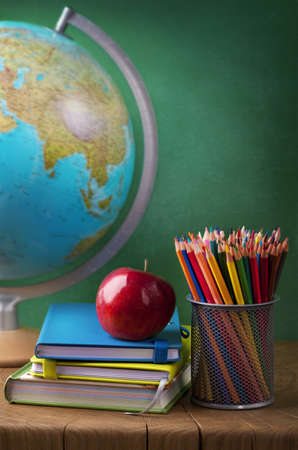 Stack of books, red apple, globe and pencils photo