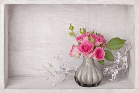 Pink roses in a vase on blue background photo