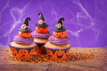 Halloween cupcake with pumpkins with witch hat photo