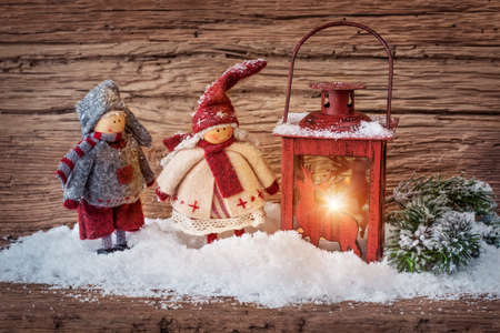 Two little santa decoration and burning lantern on wooden background photo