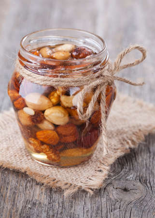 Honey and mixed nuts on wooden table Stock Photo