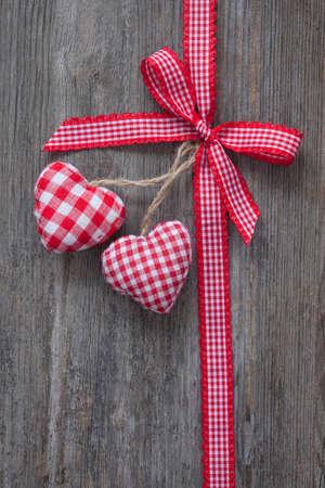 結び目: 木製の背景に心を持つ赤いリボン 写真素材