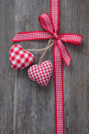 knots: Red ribbon with hearts on a wooden background