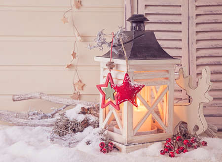 Burning lantern and christmas decoration on white background photo