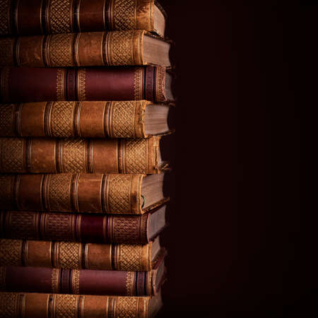 Pile of ancient books on brown background