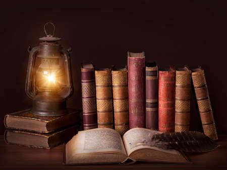 Libros antiguos y de época de pie en una fila y una vieja lámpara