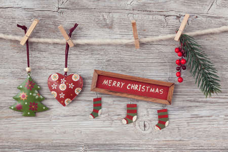 hanging on: Christmas decoration over wooden background