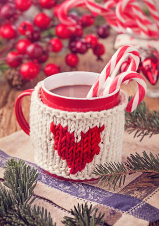 Hot chocolate with candy cane in a red mug photo