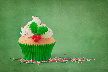 Christmas cup cakes with holly berry on a green  photo