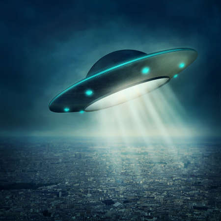 UFO flying in a dark sky Stock Photo