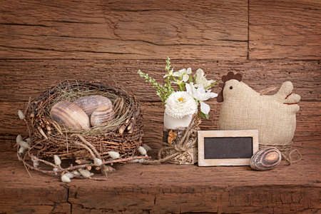 Easter eggs in nest and flowers on wooden background photo