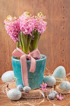 Pink hyacinths in a blue flower pot and easter eggs photo