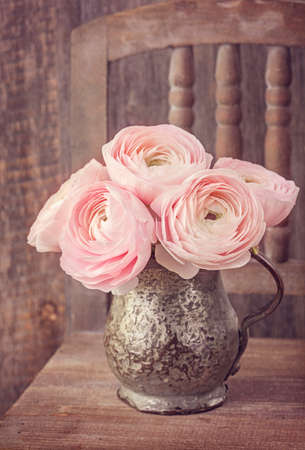 Ranunculus flowers in a old vase Stock Photo