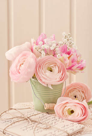 Pink ranunculus flowers and letters