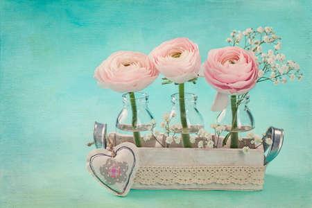 青色の背景にピンクのラナンキュラスの花